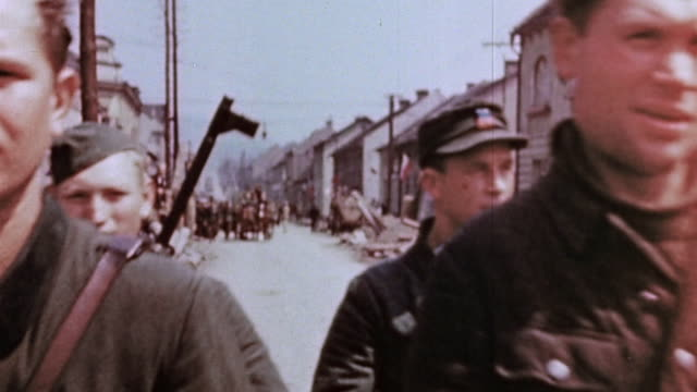 surrendered german army soldiers, some members of a hospital unit, riding in horse-drawn carts and walking through village street / czechoslovakia - horsedrawn stock videos & royalty-free footage