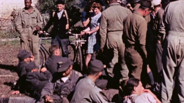 surrendered german army soldiers standing and lying on blankets smoking and waiting / france - prigioniero di guerra video stock e b–roll