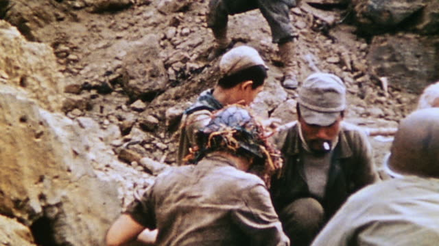 surrendered japanese soldiers sitting beside tunnel mouth with marines, talking and laughing / iwo jima, japan - pacific war video stock e b–roll
