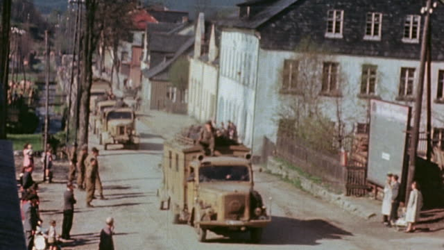 vidéos et rushes de surrendering german army driving in staff cars and trucks through village past gis waiting in back of truck and civilian serving coffee to waiting... - 1945