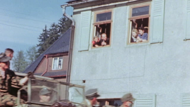 vidéos et rushes de surrendering german army driving in trucks and horse-drawn wagons through village past gis, civilians watching from second-floor window, and gis in... - 1945