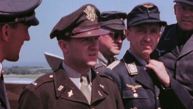 Surrendering Luftwaffe officers including HansUlrich Rudel disembarking C47 Skytrain at airport being met by US Army officers boarding open truck and...