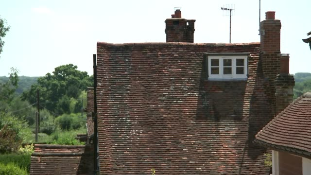 What is causing them UK Surrey houses and church in village of Newdigate and resident interview ENGLAND Surrey Newdigate EXT Houses in village Close...