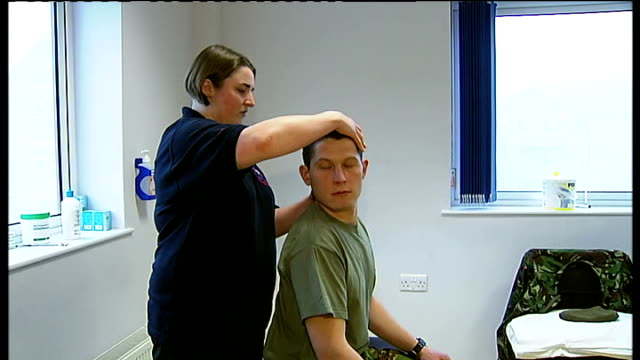 surrey pirbright barracks int lance corporal andrew ferguson receiving physiotherapy treatment on his neck reporter to camera - physiotherapy stock videos & royalty-free footage