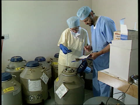 anat location unknown seq medical technicians beside churns of liquid nitrogen as remove tray of samples from one and check details against list side... - magnification stock videos & royalty-free footage