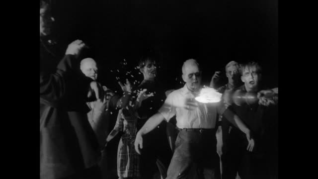 1968 A surrounded and anxious man uses fire and a shotgun to ward off zombies