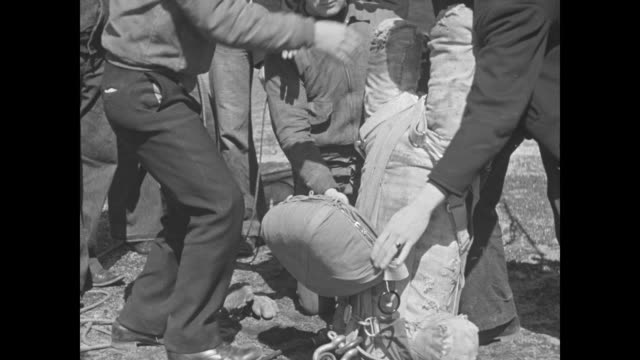 surrounded by sailors sot a man briefly explains the test men attach a heavy parachute to a dummy it's raised by a 'trapeze' to a navy airship chutes... - frayed stock videos & royalty-free footage