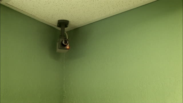 surveillance camera attached to ceiling in corner of room / moving back and forth / flashing light - corner stock videos & royalty-free footage