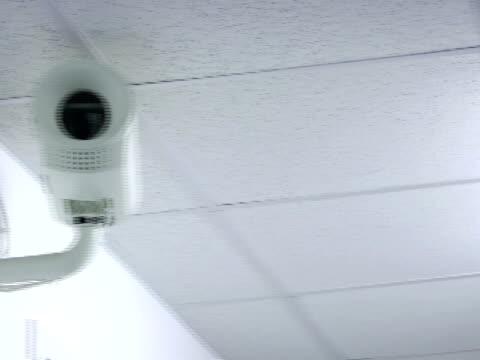 cu, pan, surveillance camera ay ceiling in office - storebror bildbanksvideor och videomaterial från bakom kulisserna