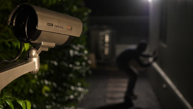 cctv surveillance camera capture scene of thief jump down and try to break into a house at night - camera photographic equipment stock videos and b-roll footage