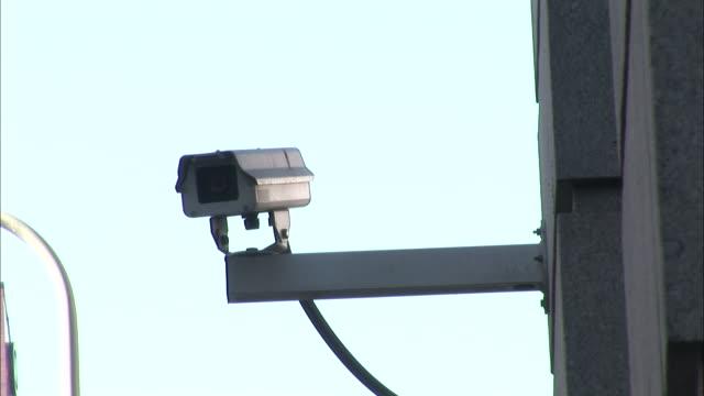 vidéos et rushes de a surveillance camera is mounted on a metal beam that extends from a large building. - sécurité