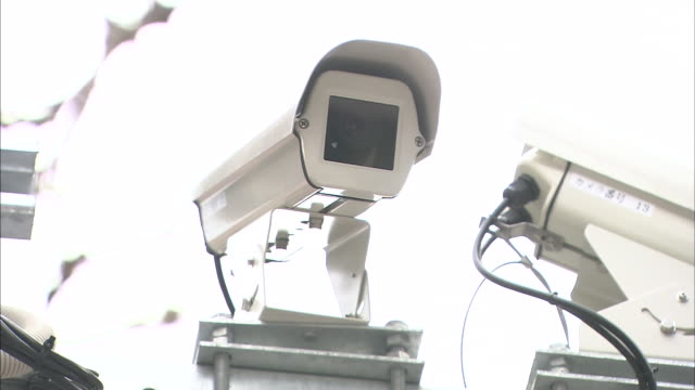A surveillance camera is positioned to observe a city street.