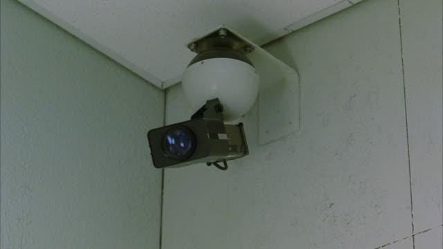 cu surveillance camera mounted on ceiling of room - övervakningskamera bildbanksvideor och videomaterial från bakom kulisserna
