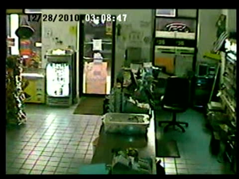 / surveillance camera showing inside of convenience store / man wearing hoodie rushes into store carrying a giant long piece of wood / store clerk... - criminal stock videos and b-roll footage