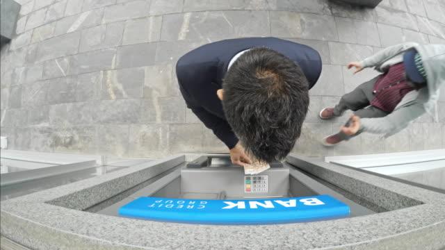 überwachungsmaterial eines kaufmanns machen eine barentnahme von atm und beraubt bei hellem tageslicht - stehlen verbrechen stock-videos und b-roll-filmmaterial