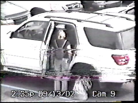 / surveillance pole camera footage woman walking with small child to car in parking lot woman looks all around her lifts child into car seat in... - mädchen stock-videos und b-roll-filmmaterial