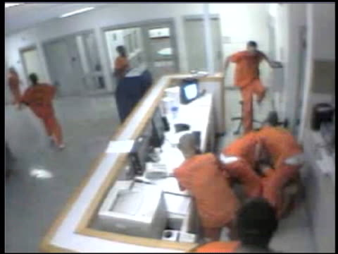 / surveillance video inside prison deputy sitting at his desk when an inmate in orange jumpsuit comes out of nowhere and proceeds to choke him /... - jumpsuit stock videos & royalty-free footage
