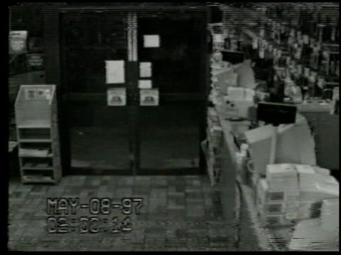/ surveillance video man comes into convenience store suddenly reaches around register grabs cash register and tries to walk out door with it but...