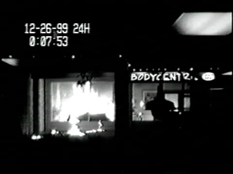 vídeos de stock, filmes e b-roll de / surveillance video of man outside on street in front of a business / man throws something like a molotov cocktail through window it bursts into... - autoimolação