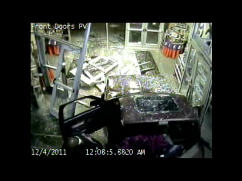 vídeos de stock, filmes e b-roll de / surveillance video of truck crashing through storefront and then thief fills up the back of the pickup truck with stolen goods and crashes back out... - imagem em movimento
