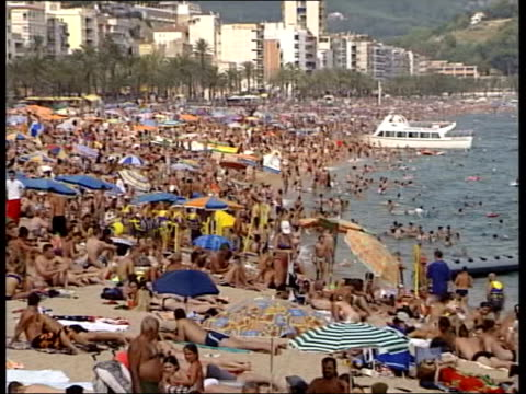 survey attacks big package holiday companies; lib spain: ext gv people on crowded beach people playing in the sea lib ???: int people dancing in... - jug stock videos & royalty-free footage