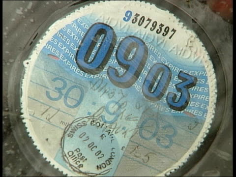 RAC Survey on tax disc cheats ITN London Tax disc for 2004 displayed on car windscreen ZOOM CSs Road tax discs for 2004 on windscreens CS Tax disc...