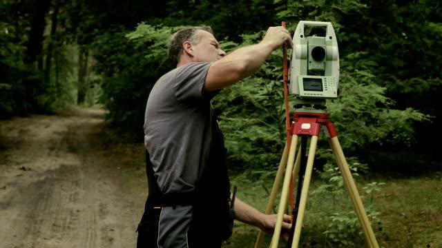 surveying an area of land - trigonometrie stock-videos und b-roll-filmmaterial
