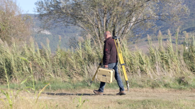 Surveyor Carrying His Equipment to the Car