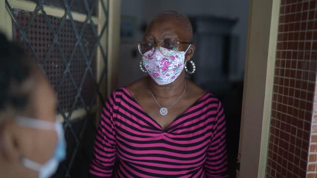 surveyor talking to senior woman in the doorway - wearing face masksurveyor talking to senior woman in the doorway - wearing face mask - doorway stock videos & royalty-free footage