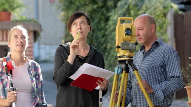 vermesser planung auf stadtstraße vor der messung - messen stock-videos und b-roll-filmmaterial