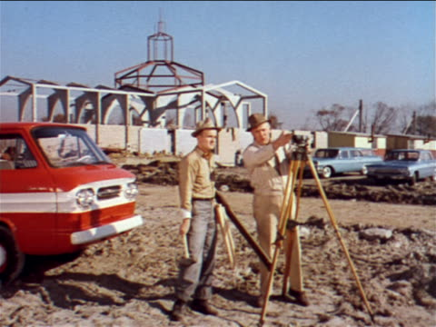 1962 2 surveyors standing on construction site talking + looking at surveyor's levels / industrial - surveyor stock videos and b-roll footage