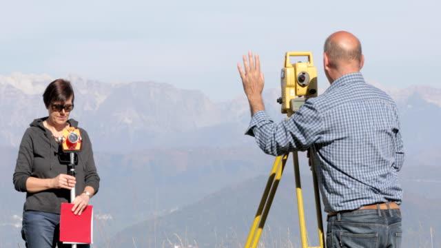 vídeos y material grabado en eventos de stock de peritos trabajan en la cima de una colina - encuadre de tres cuartos