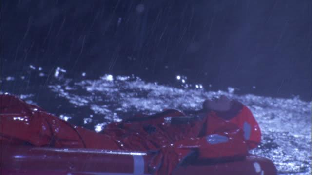 a survivor lies on a life raft during an ocean storm. - 生存点の映像素材/bロール