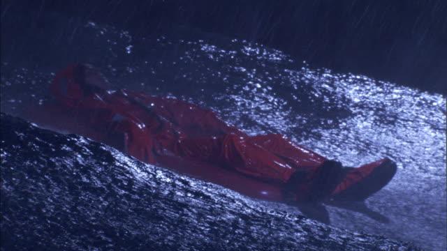a survivor lies on a life raft during an ocean storm. - überleben stock-videos und b-roll-filmmaterial