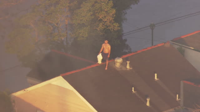 survivor standing on rooftop and watching house burning with fire / united states - hurricane katrina stock videos and b-roll footage