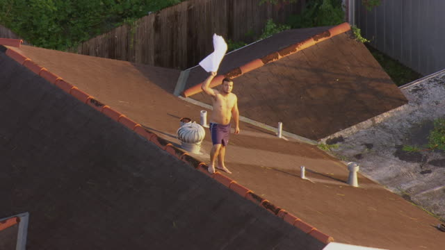 survivor standing on rooftop and waving cloth for rescue help / united states - hurricane katrina stock videos and b-roll footage