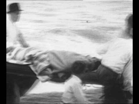 survivors of ss morro castle wade through waves after swimming to shore people on beach meet them / montage men bear rescued woman on stretcher to... - ship launch stock videos and b-roll footage