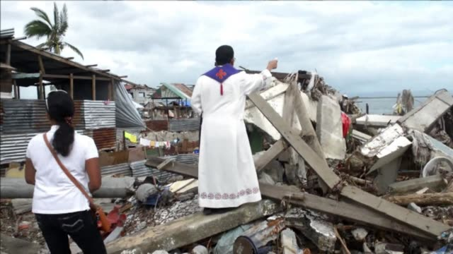 survivors of super typhoon haiyan gather to pray while a priest sprinkles holy water on their ruined homes in a ceremony marking the end of a 40-day... - holy water stock videos & royalty-free footage