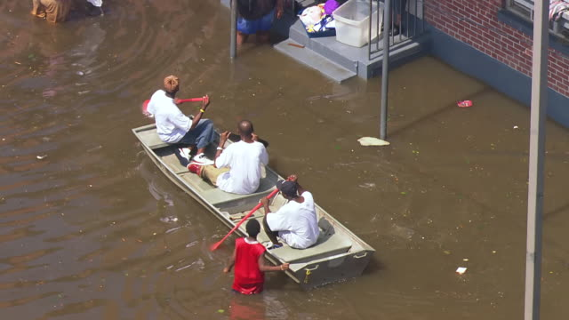 survivors on small boat paddling near french quarter and sick woman in apparent pain being floated through flood waters in large orange container /... - new orleans stock videos & royalty-free footage
