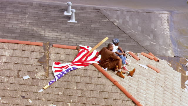 survivors sitting on rooftop of house waiting for rescue help view of american flag lying on rooftop / united states - hurricane katrina stock videos and b-roll footage