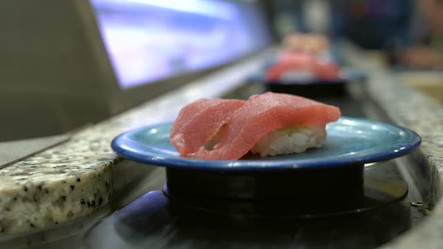 sushi and sashimi. dishes of sushi and sashimi rolling on conveyer belt.japanese traditional lifestyle. - sushi video stock e b–roll