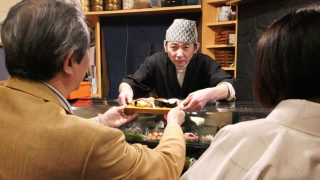 sushi chef in small tokyo restaurant - sushi video stock e b–roll