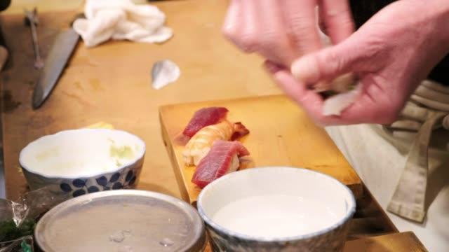 vídeos de stock e filmes b-roll de sushi chef in small tokyo restaurant - sushi
