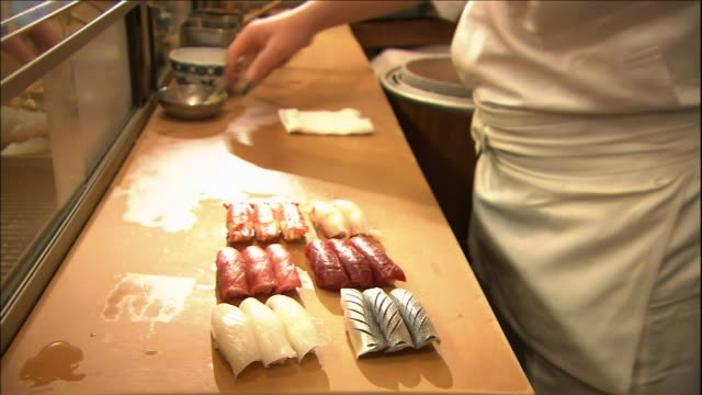 A sushi chef prepares sushi at a sushi bar.