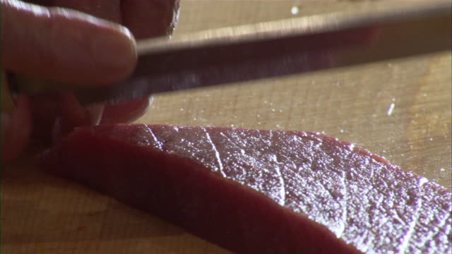 ECU Sushi Preparation, man's hand cutting piece of raw fish with sharp knife and placing it on cutting board / Oma, Aomori Prefecture, Japan