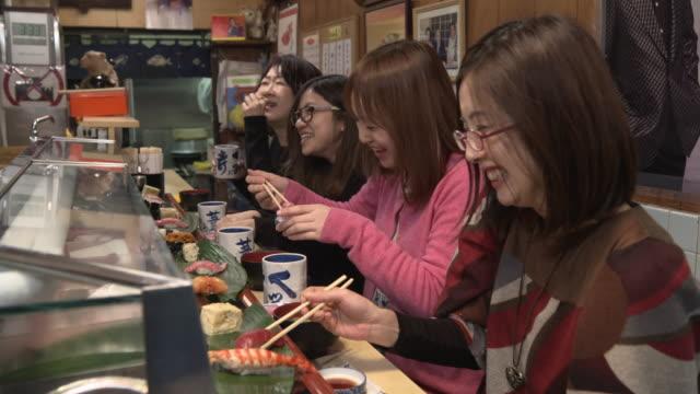 sushi restaurant - tsukiji market tokyo, japan - 若い女性点の映像素材/bロール