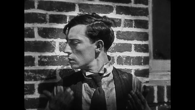 1920 suspect (buster keaton) bewilders policeman (eddie cline) by turning to show him a half white half black face before running away - criminal stock videos & royalty-free footage