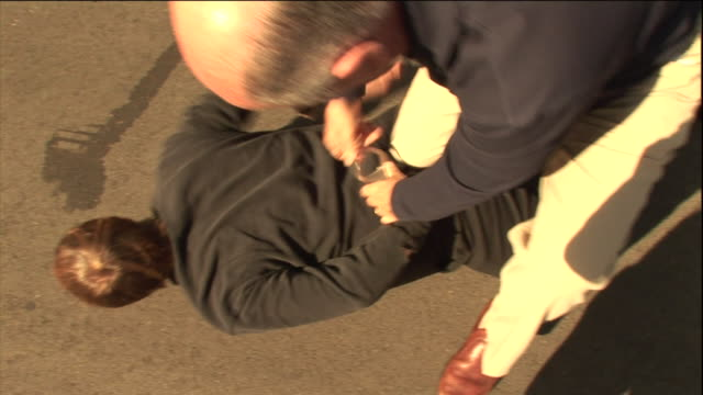 a suspect lies face down as a police officer applies handcuffs. - face down stock videos & royalty-free footage