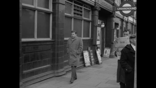 montage suspicious man spying on two people and reading newspaper on sidewalk / london, england, united kingdom - 1962 stock videos & royalty-free footage