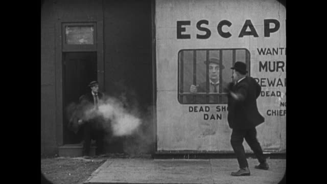 1921 suspicious policeman compares worried man (buster keaton) to wanted poster before being shot by man behind him - 1921年点の映像素材/bロール